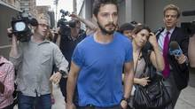 "Actor Shia LaBeouf walks through the media after leaving Midtown Community Court following his arrest Thursday for yelling obscenities at the Broadway show ""Cabaret,"" Friday, June 27, 2014, in New York. (John Minchillo/AP)"