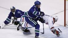 Montreal Canadiens' Max Pacioretty dives through the air after being checked by Vancouver Canucks' Dan Hamhuis in front of Canucks goaltender Roberto Luongo during the third period of their NHL hockey game in Vancouver, British Columbia March 10, 2012. (BEN NELMS/REUTERS/BEN NELMS/REUTERS)