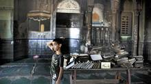 An Arab-Israeli boy inspects a burnt mosque after it was torched in the northern Israeli Bedouin village of Tuba-Zangariya on Monday. (Menahem Kahana/AFP/Getty Images)