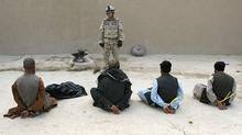 A Canadian soldier guards six of ten suspected Taliban prisoners captured in a raid on a compound in northern Kandahar province on May 10, 2006. (JOHN D MCHUGH)
