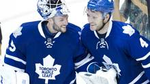 The Toronto Maple Leafs Jonathan Bernier and Cody Franson celebrate their team's win following the shootout to decide the winner of the Leafs season opener against the Ottawa Senators at the ACC in Toronto on Oct. 5, 2013. (Peter Power/The Globe and Mail)