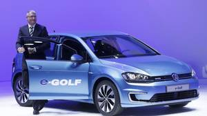 Volkswagen's Heinz-Jacob Neuber stands next to an e-Golf electric vehicle during the press preview day of the North American International Auto Show in Detroit, Michigan January 13, 2014.