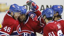 Montreal Canadiens centre Scott Gomez is congratulated by teammates Andrei Kostitsyn, Raphael Diaz and Chris Campoli during the second period of play of their NHL pre-season game against Tampa Bay Lightning at the Colisee in Quebec City, October 1, 2011. (MATHIEU BELANGER/Reuters)