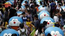 Visitors to a 2012 exhibit in Hong Kong inspect 100 figures, each showing Doraemon – Japan's first anime cultural ambassador – in a different pose. After 45 years, the Japanese icon's tales have been translated into English. (BOBBY YIP/REUTERS)