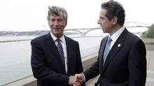 New York Gov. Andrew Cuomo, right, shakes hands with Ambassador Gary Doer of Canada after announcing a Peace Bridge deal in Buffalo, N.Y., Wednesday, June 26, 2013. (David Duprey/AP)