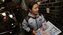 A worker loads newspapers for delivery just after 2 a.m. in Tokyo. (Nathan VanderKlippe/The Globe and Mail)