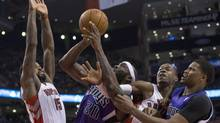 Sacramento Kings' Reggie Evans (centre left) shoots on Toronto Raptors' Amir Johnson as Raptors Terrence Ross (centre right) and Kings' Rudy Gay look on during first half NBA basketball action in Toronto on Friday March 7. (Chris Young/THE CANADIAN PRESS)