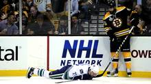 Mason Raymond of the Vancouver Canucks lays on the ice after being checked by Johnny Boychuk of the Boston Bruins. (Harry How/Harry How/Getty Images)