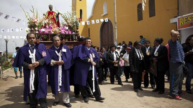 People carry the statue of Santa Efigenia during a procession in La Quebrada, Peru, in late September. Every year, Peruvians descended from African slaves come to La Quebrada to celebrate the adored black saint, the only African saint venerated in Peru. (Rodrigo Abd/AP)