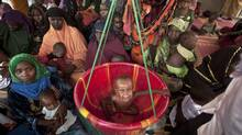 Brahim Abba, 2, has his weight checked in a scale as other mothers and children wait their turn, at a walk-in feeding center in Mao, capital of the Kanem region of Chad, Tuesday, April 17, 2012. (AP Photo/Ben Curtis) (Ben Curtis/AP)