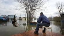 Gerald Racine, the lone resident staying in his his flooded neighbourhood looks out his street in St-Paul-de-I'Ile-aux-Noix, May 6, 2011. (Christinne Muschi for The Globe and Mail)