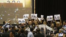 """Pro-democracy lawmakers hold up a banner and signs during a protest as Li Fei (seen on screen), deputy general secretary of the National People's Congress (NPC) standing committee, speaks during a briefing session in Hong Kong September 1, 2014. Pro-democracy activists vowed on Sunday to bring Hong Kong's financial hub to a standstill after China's parliament rejected their demands for the right to freely choose the former British colony's next leader in 2017. The banner reads """"Protest against the lost of credit on central government. It's shameful on the deprivation of democracy."""" The signs read, """"shameful"""". REUTERS/Bobby Yip (CHINA - Tags: POLITICS CIVIL UNREST TPX IMAGES OF THE DAY) (BOBBY YIP/REUTERS)"""