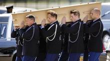 Pallbearers at Eindhoven airbase in the Netherlands carry a coffin toward a hearse on July 23, 2014, during a ceremony to mark the return of the first bodies of passengers and crew killed in the downing of Malaysia Airlines Flight 17. (PHIL NIJHUIS/ASSOCIATED PRESS)