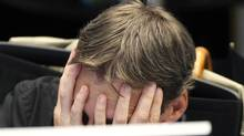 A broker covers his face behind his screen at the stock market in Frankfurt, Germany, Monday, Aug.8, 2011, where the stock index went down after the opening of the stock market. (Michael Probst/AP)