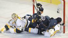 Edmonton Oilers' Lennart Petrell, centre, and Nashville Predators Craig Smith, right, crash the net of goalie Anders Lindback, during second period NHL hockey action in Edmonton, on Monday, November 28, 2011. THE CANADIAN PRESS/John Ulan (John Ulan/CP)