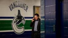 Vancouver Canucks' owner Francesco Aquilini speaks on his mobile phone as general manager Mike Gillis, not pictured, speaks to reporters down the hallway in Vancouver, B.C., on Monday April 25, 2011. Vancouver and the Chicago Blackhawks play game 7 of a Western Conference quarterfinal Stanley Cup playoff series Tuesday. (DARRYL DYCK/THE CANADIAN PRESS)