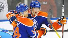 Edmonton Oilers' Ryan Nugent-Hopkins, right, celebrates his goal against the New York Rangers with teammate Jordan Eberle during second period NHL hockey action in Edmonton on Saturday, (John Ulan/The Canadian Press)