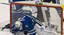 Vancouver Canucks Aaron Rome, left, punches Colorado Avalanche Cody McLeod after the two fell to the ice, knocking the net into Canucks goalie Roberto Luongo during the first period in Vancouver. (ANDY CLARK/Andy Clark /Reuters)