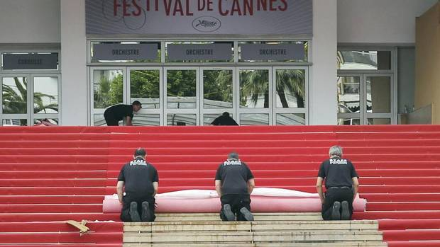 Workers install the red carpet in front of the main entrance of the Festival Palace for the opening ceremony of the 66th Cannes Film Festival in Cannes May 15, 2013. (Regis Duvignau/Reuters)