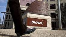 People walk past the headquarters of Shaw Communications in Calgary, Alta., Wednesday, April 13, 2011. (Jeff McIntosh/THE CANADIAN PRESS)