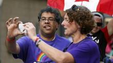 Calgary Mayor Naheed Nenshi and another marcher take a photo while marching in a gay pride parade in Calgary, Alta., Sunday, Sept. 1, 2013. (Jeff McIntosh/THE CANADIAN PRESS)