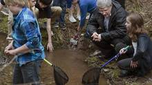 Prime Minister Stephen Harper visits a stream with young students in New Maryland, N.B. on Thursday, May 15, 2014. (Andrew Vaughan/THE CANADIAN PRESS)