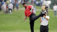 Tiger Woods makes an awkward follow through after hitting from the lip of a fairway bunker on the second hole during the final round of the Bridgestone Invitational (Mark Duncan/AP)