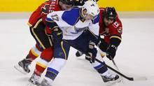Calgary Flames' Mike Cammalleri (L) and Mark Giordano (R) attempt to get the puck from St. Louis Blues' Vladimir Sobotka during the second period of their NHL hockey game in Calgary, Alberta, February 15, 2013. (TODD KOROL/REUTERS)