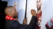 Toronto FC new soccer player Jermain Defoe signs a poster after a news conference announcing his incorporation to the club, Toronto, January 13, 2014. (Fernando Morales/The Globe and Mail)