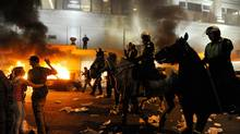 Police on horseback ride through the street past a fire on June 15, 2011 in Vancouver. (Rich Lam/AFP/Getty Images)