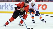 Ottawa Senators' Milan Michalek skates the puck past New York Islanders' Brian Strait during second period pre-season NHL hockey action in Ottawa on Sunday, Sept. 29, 2013 (The Canadian Press)