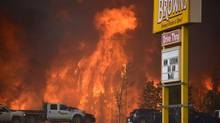 A wall of fire rages outside of Fort McMurray, Alta., Tuesday May 3, 2016. Raging forest fires whipped up by shifting winds sliced through the middle of the remote oilsands hub city of Fort McMurray Tuesday, sending tens of thousands fleeing in both directions and prompting the evacuation of the entire city. (Terry Reith/THE CANADIAN PRESS)