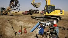 Workers install a 5 inch natural gas collector pipeline to a coalbed methane gas well, owned by Encana, near Lyalta, Alberta . (LARRY MACDOUGAL/The Canadian Press)
