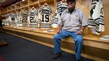 """Fred Sasakamoose, a residential school survivor and the first First Nations NHL hockey player, sits in the Vancouver Giants dressing room where the WHL hockey team unveiled First Nations tribute jerseys in Vancouver, Sept. 19, 2013. The jerseys feature the """"lazy cross"""", the brand of the Alkali Lake Ranch where most players on the Alkali Lake Braves hockey team worked. Sasakamoose played for the Chicago Blackhawks in 1954. The Giants will wear the jerseys on Friday when they open their season against the Victoria Royals. (DARRYL DYCK FOR THE GLOBE AND MAIL)"""