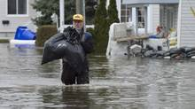 A man carries a bag of his belongings as he walks along a flooded road, Monday May 8, 2017 in Gatineau, Que. (Adrian Wyld/THE CANADIAN PRESS)