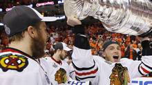 Chicago Blackhawks' Patrick Kane hoists the Stanley Cup beside teammates Kris Versteeg (L) after scoring the winning goal against the Philadelphia Flyers during overtime in Game 6 of the NHL Stanley Cup final hockey series in Philadelphia June 9, 2010. REUTERS/Shaun Best (SHAUN BEST)
