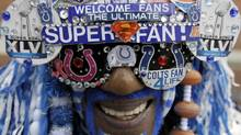 """Football fan Michael Hopson is dressed as """"Super Fan"""" as he walks in Super Bowl Village, Friday, Feb. 3, 2012, in Indianapolis, Ind. The New England Patriots are scheduled to face the New York Giants in NFL football Super Bowl XLVI on Feb. 5. (AP Photo/Mark Humphrey) (Mark Humphrey)"""