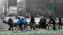 Cyclists use a separated bike lane in Vancouver. The city has been able to shift 50 per cent of all urban trips to biking, walking or transit in recent years. (DARRYL DYCK for The Globe and Mail)