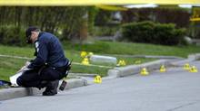 A member of the provinces Special Investigations Unit (SIU) picks up evidence at a crime scene in Toronto, April 16, 2012. (J.P. MOCZULSKI/The Globe and Mail)