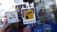 Toronto, Nov. 11/09 - A customer walks past an Interac sign on the Petro Plus Variety Store on Queen Street East in Toronto, Ontario, Canada. Interac says it is experiencing technical problems with its e-Transfer system, mainly affecting deposits. (Deborah Baic/The Globe and Mail)