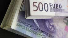 Stacks of Swiss franc and euro banknotes are displayed in Bern August 15, 2011. (PASCAL LAUENER/REUTERS)