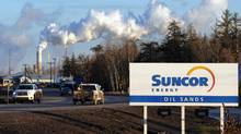 Workers leave the Suncor oil sands extraction facility near the town of Fort McMurray, Alta., in this file photo. (MARK RALSTON/AFP/Getty Images)