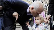NDP leader Jack Layton kisses his granddaughter Beatrice after casting his ballot in the federal election in Toronto on May 2, 2011. Layton, 61, the charismatic leader of Canada's official opposition, died on August 22, 2011 just months after guiding his New Democratic Party to its strongest ever performance in the May federal election. (MARK BLINCH/Reuters)