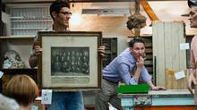 David Amer, co-owner of Mrs. Huizenga's on Roncesvalles Ave. in Toronto, presents a framed vintage photo for bidding at the shop's twice-monthly auction. (Galit Rodan/The Globe and Mail)