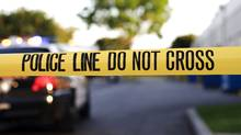 A Blurred Police Car In The Background Behind Yellow Crime Scene Tape. (John Roman)