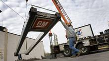 Workers remove some of the old signage at a GM dealership in Toronto. (Peter Power/The Globe and Mail)