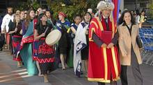 SFU Chancellor Milton Wong and first nations student centre director Sasha Hobbs lead students to a feast following a First Nations convocation ceremony in 2003. (SFU photo/SFU photo)