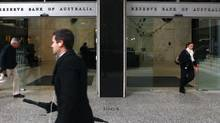 People walk past the Reserve Bank of Australia in Sydney, Tuesday, June 5, 2012. Australia's central bank has cut its benchmark interest rate for a second consecutive month, lowering it a quarter percentage point to 3.5 per cent. (Rick Rycroft/AP)