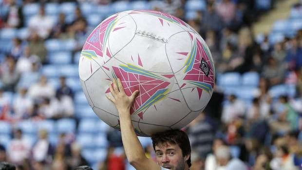 A volunteer holds up a big ball as he prepares to kicks it to the fans prior to the quarter-final women's soccer match between Britain and Canada at the 2012 London Summer Olympics, in Coventry, England, Friday, Aug. 3, 2012. (Hussein Malla/AP)