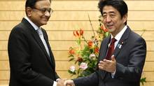 India's Finance Minister Palaniappan Chidambaram, left, is greeted by Japan's Prime Minister Shinzo Abe during his courtesy call at Abe's official residence in Tokyo Monday, April 1, 2013. (Issei Kato/AP)